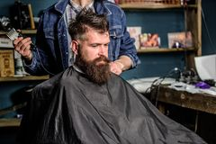 Barber preparing hair clipper for bearded man, barbershop background. Barber with clipper and brutal bearded client royalty free stock photos
