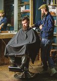 Barber preparing hair clipper for bearded man, barbershop background. Barber with clipper and brutal bearded client. Hipster client covered with cape waiting royalty free stock photos