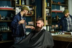 Barber preparing hair clipper for bearded man, barbershop background. Barber with clipper and brutal bearded client stock photos