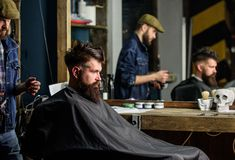 Barber preparing hair clipper for bearded man, barbershop background. Hipster client covered with cape getting haircut royalty free stock photography