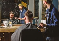 Barber preparing hair clipper for bearded man, barbershop background. Hipster lifestyle concept. Hipster client covered. With cape getting haircut. Barber with stock images