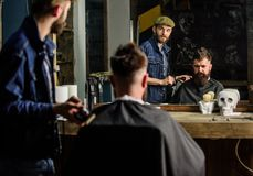 Barber preparing hair clipper for bearded man, barbershop background. Hipster lifestyle concept. Hipster client covered royalty free stock photos