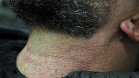 Barber rakar skägget på en äldre man med grå hårrakkniv lager videofilmer