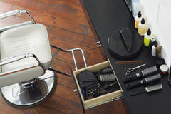 Barber's chair beside open draw of hair products, scissors and hairbrushes in salon, overhead view Stock Photography