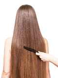Barber's hand combing her long straight hair  on white. Royalty Free Stock Photography