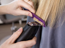 Barber's hands trimming the ends of hair Stock Image