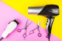 Barber Scissors profissional à moda, tosquiadeiras elétricas brancas e secador de cabelo no fundo amarelo e cor-de-rosa Sal?o de  foto de stock