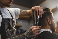 Barber with scissors at work stock images
