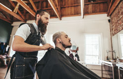 Barber serving client in hair salon stock photography