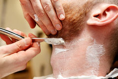 Barber shave and modeling beard at the hair salon Stock Image