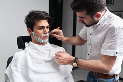 Barber shaves beard with razor and shaving foam Stock Images
