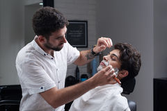 The barber shaves beard with razor and shaving foam Stock Images
