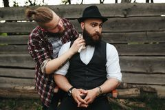 Barber shaves a bearded man Stock Images