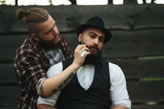 Barber shaves a bearded man Royalty Free Stock Photo