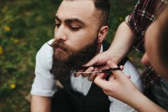 Barber shaves a bearded man Royalty Free Stock Photos