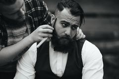 Barber shaves a bearded man Stock Photo