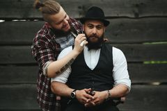 Barber shaves a bearded man Outdoors Stock Photos