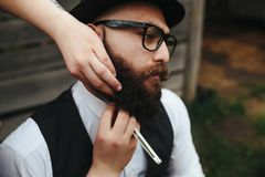 Barber shaves a bearded man Royalty Free Stock Photography