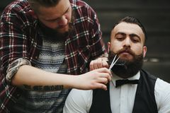 Barber shaves a bearded man Stock Photos