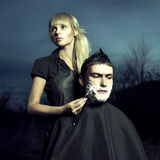 Barber shaves client Stock Photography