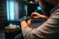 Barber shaves the hair by straight razor Stock Photo