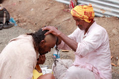 Barber shaves the head of a devotee Stock Images
