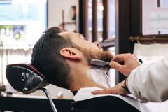 A barber shaves his client`s beard in the traditional way stock photos