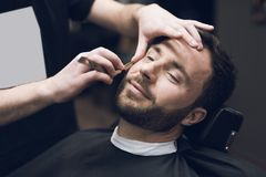 The barber shaves his head, mustache and beard to the man in the barbershop. The barber shaves his head, mustache and beard to the men in the barbershop. The Stock Photo