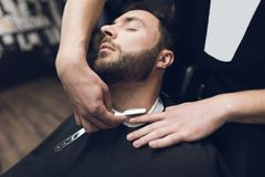 The barber shaves his head, mustache and beard to the man in the barbershop. The barber shaves his head, mustache and beard to the men in the barbershop. The Stock Image