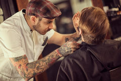 Barber shaving beard Stock Images