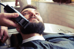 Barber shaving beard. With electric razor in vintage barber shop stock photos