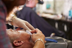 Barber Shaving Client With Cut Throat Razor Stock Photos