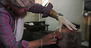 Barber Shaving Client With Cut Throat Razor. Hairdresser shaving client's beard with cut throat razor.Shot on Sony FS700 at frame rate of 25fps stock video