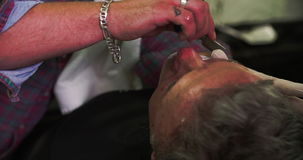 Barber Shaving Client With Cut Throat Razor. Hairdresser shaving client's beard with cut throat razor.Shot on Sony FS700 at frame rate of 25fps stock video footage
