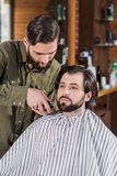 Barber shaving client with Hair Clipper. At barbershop royalty free stock photography