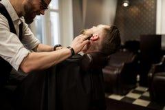 Barber shaving client neck with razor. Portrait of barber shaving client neck with razor Royalty Free Stock Image