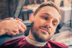 Barber shaving a client with trimmer Royalty Free Stock Photography