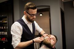 Barber shaving customer with razor. Portrait of barber shaving customer with razor Stock Photo