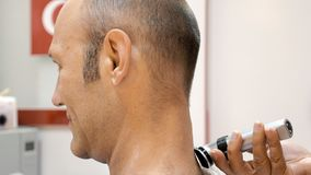 Barber is shaving his client in old fashion manner stock image