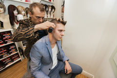 Barber shaving male customer's hair in shop Royalty Free Stock Image