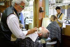 2019-02-11 Argentina Session of haircut and shave of two men with two barbers stock photography