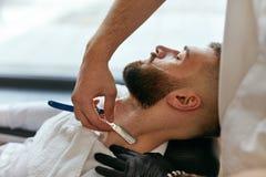 Barber Shaving Man Beard With rak rakkniv i Barber Shop arkivfoto