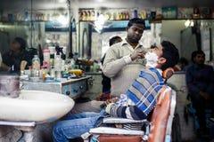 Barber shaving man in Delhi Stock Images