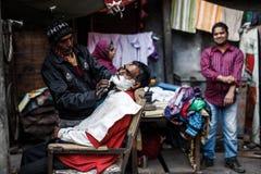 Barber shaving man in Delhi Stock Photography