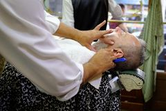 2019-02-11 Argentina Session of haircut and shave of two men with two barbers royalty free stock images