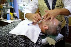 2019-02-11 Argentina Session of haircut and shave of two men with two barbers royalty free stock photo