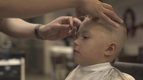 Barber with shaving razor doing boy hairstyle in male salon. Childen hairstyle concept. Hairdresser using straight razor. For shave hair little boy. Hairstylist stock video footage