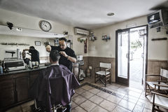 Barber shaving with a razor to young man in a barber's shop Stock Photography