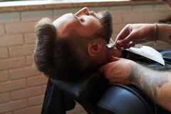 Barber shaving with vintage straight razor Royalty Free Stock Image