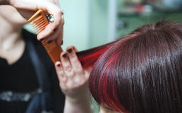 Barber shears brunette woman with red hair strands Royalty Free Stock Photos